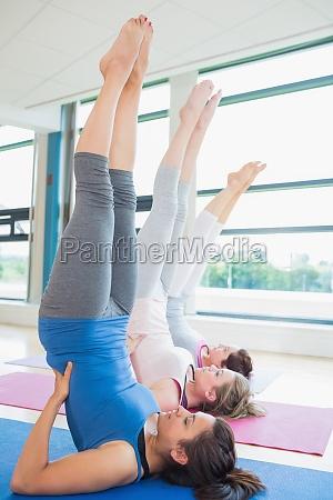 frauen die rueckseiten am yogakurs im