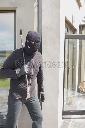 einbrecher versteckt sich hinter wand mit