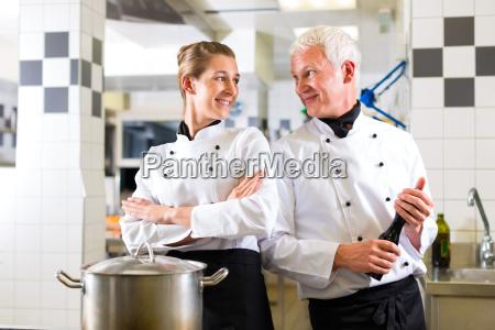 two cooks team in restaurant kitchen