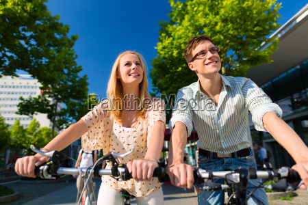 couple in city rides with bicycle