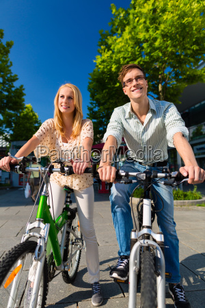 paar in stadt faehrt mit fahrrad