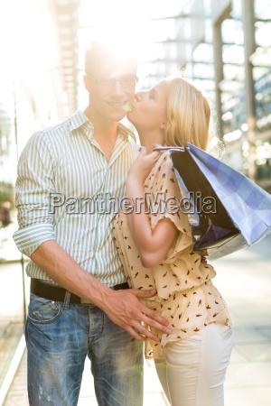 frau kuesst mann beim einkaufen und