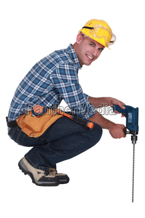 tradesman using a power tool with