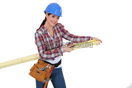 female carpenter measuring a piece of