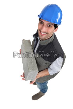 mason carrying a breeze block