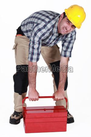 builder kaempfen schwere werkzeugkasten zu heben