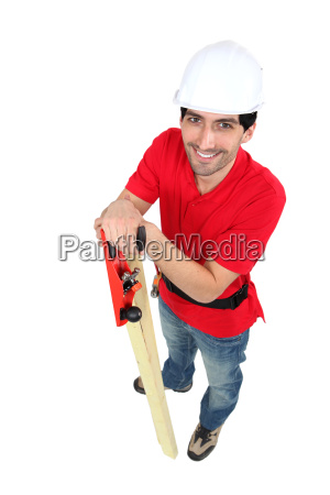 craftsman holding a wooden board and