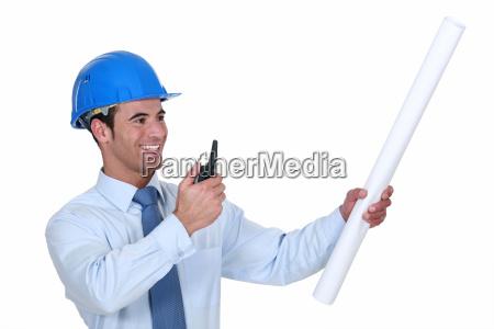 architekt mit funkempfaenger und plaenen