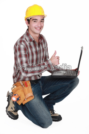 happy builder with laptop giving the