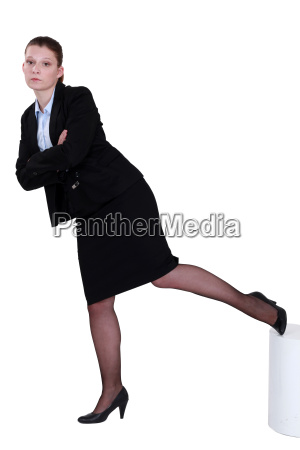 stern businesswoman standing on one leg