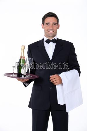 smart kellner haelt tablett mit champagnerglaesern