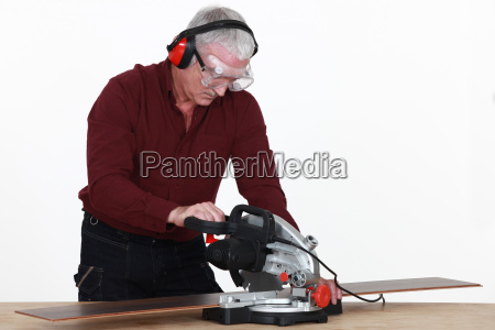 craftsman cutting a board with an