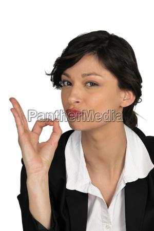 brunette businesswoman giving ok sign