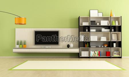 gruenes wohnzimmer mit fernseher und buecherregal