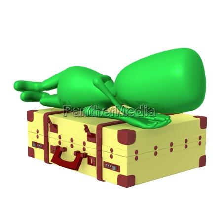 puppe schlafend auf grossem koffer schlafend