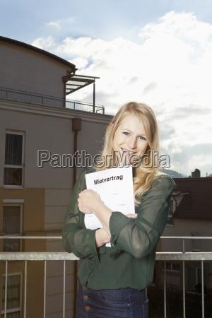 junge frau am balkon klammert ihren