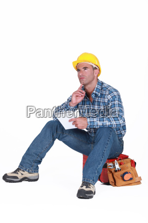 builder sat on tool box thinking