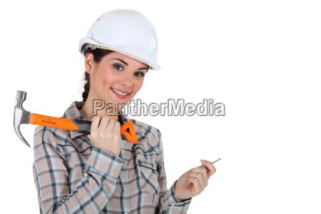 tradeswoman holding a nail and hammer