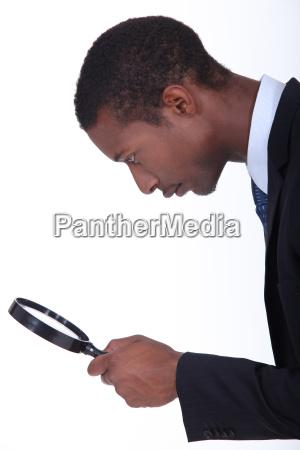 black man looking through a magnifying