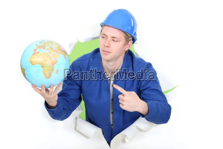 young apprentice in jumpsuit pointing at