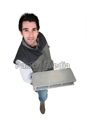 bricklayer standing with concrete block against