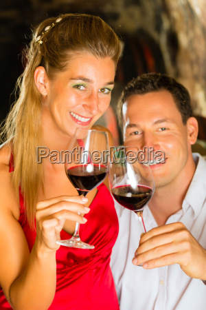 man and woman are tasting wine