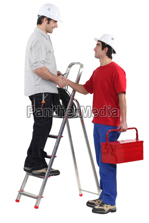 two workers greeting each other with