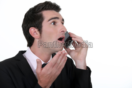 shocked businessman with mobile telephone