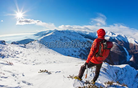 mountaineer while observing a mountain panorama