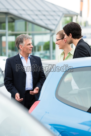 car dealers and customers look at
