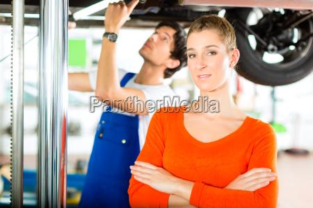 car mechanic repairing car of customer