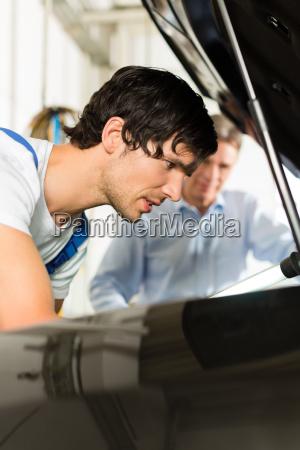 customer and mechanic at car look