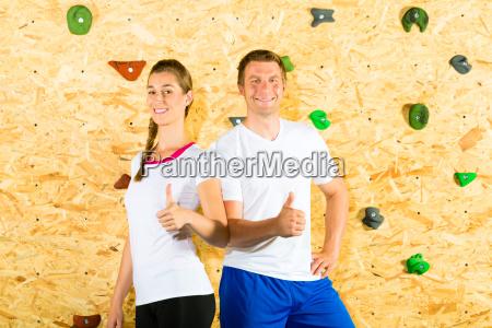 frau und mann klettern in kletterhalle