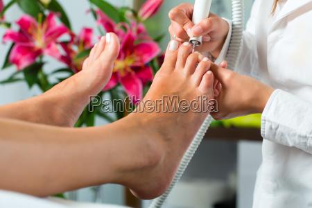 frau in kosmetikstudio erhaelt pedikuere