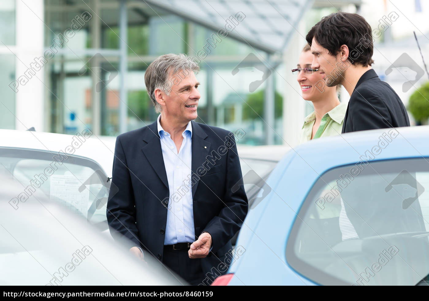 Autohändler Und Kunden Schauen Ein Auto An Stockfoto 8460159