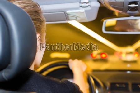 junge frau faehrt auto im tunnel