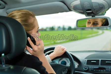 young woman with phone in car