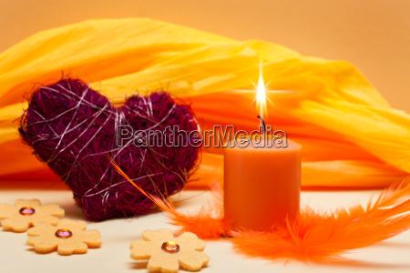 orangener hintergrund mit kerze und herz