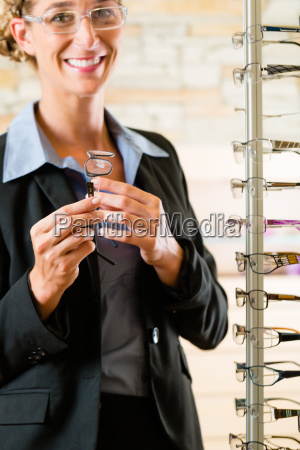 young woman buys glasses at the