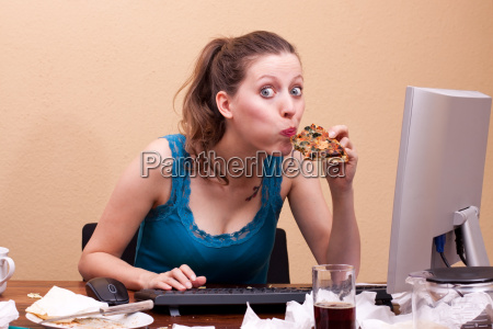 young woman eating pizza at work