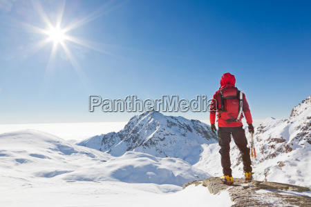 mountaineer looking at a snowy mountain