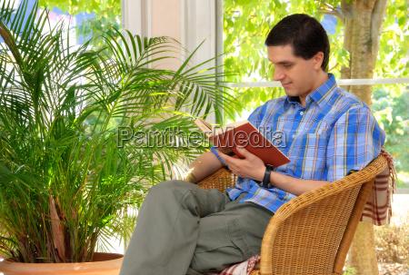 mann liest genuesslich im freundlichen wohnzimmer
