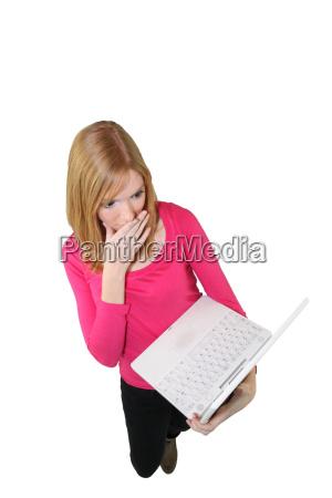 schockierte frau schaut auf computer bildschirm
