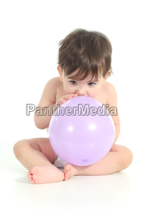 baby trying to inflate a balloon