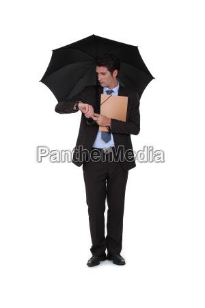 a businessman under an umbrella looking