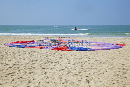 paragliding parachute laid in the sand