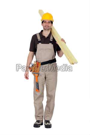 a builder carrying wooden planks