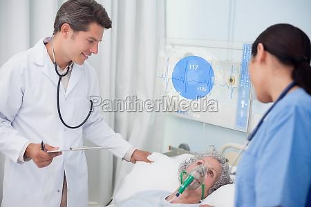 arzt und krankenschwester ueberpruefung liegenden patienten