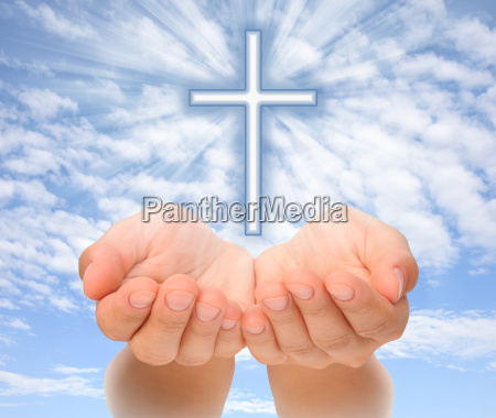 hands holding christian cross with light