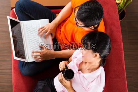 asiatisches paar auf der couch mit